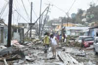 Lead image shows a road in the Roseau area is littered with structural debris, damaged vegetation and downed power poles and lines. By Roosevelt Skerrit from Vieille Case, Dominica - Morning after Hurricane Maria, Public Domain.